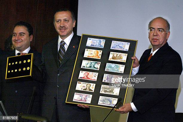 Turkish Prime Minister Recep Tayyip Erdogan holds with the president of Turkey's Central Bank Sureyya Serdengecti a board featuring the new Turkish...