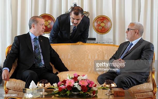 Turkish Prime Minister Recep Tayyip Erdogan talks to an interpreter as he sits alongside Moroccan Prime Minister Abdelilah Benkirane at Rabat airport...