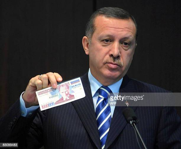 Turkish Prime Minister Tayyip Erdogan displays an banknote of the old Turkish Lira at a news conference in Ankara October 3, 2008. Turkey will return...