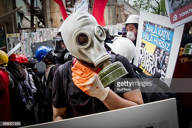 Turkish protesters wearing a gas mask and a hard hat takes cover during clashes with riot police who prevent demonstrators from reaching Taksim...