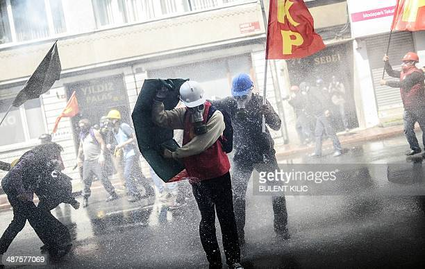 Turkish protesters wearing gas masks and hard hats take cover as riot police use a water cannon to disperse a May Day rally in Taksim Square in...