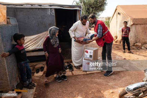 Turkish Red Crescent officer gives an aid package to a displaced Syrian family in Idlib Province on September 17 2019 in Ad Dana Syria Turkey's...