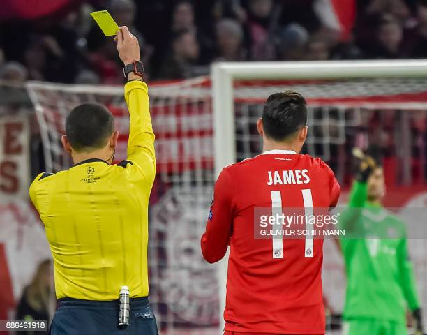 Turkish referee Cuneyt Cakir shows Bayern Munich's Columbian midfielder James Rodriguez the yellow card during the UEFA Champions League football...