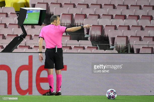 Turkish referee Cuneyt Cakir VAR replay on the fault made on Barcelona's Argentine forward Lionel Messi during the UEFA Champions League round of 16...