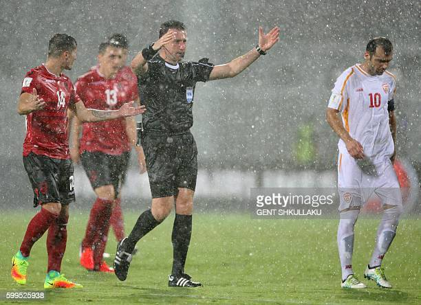 Turkish referee Huseyin Gocek interrupts the match because of heavy rainfall during the World Cup 2018 football qualification match between Albania...