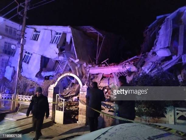 TOPSHOT Turkish rescue services and police inspect the scene of a collapsed building following a 68 magnitude earthquake in Elazig eastern Turkey on...