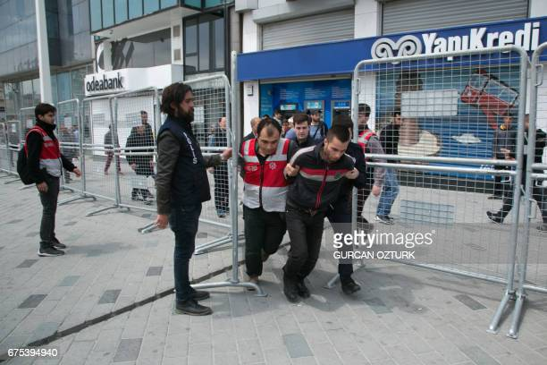 Turkish riot police arrest a protester seeking to defy a ban and march to Istanbul's Taksim square to celebrate May Day in Istanbul on May 1, 2017....
