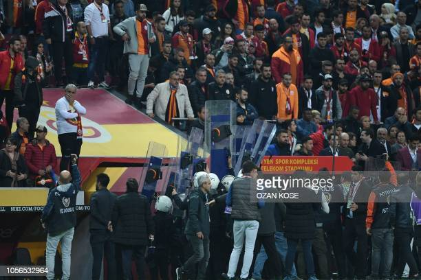 Turkish riot police officers use their shields as players leave the pitch at the end of the Turkish Spor Toto Super league fotball match between...