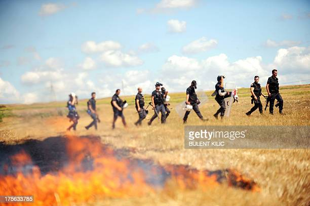 Turkish riot police walk behind flames during clashes with demonstrators near a courthouse in Silivri near Istanbul on August 5 after a court...
