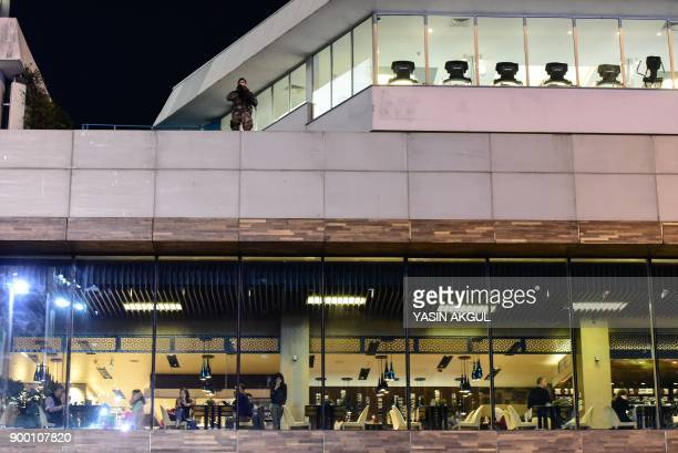 A Turkish security force member stands on the roof of a building overlooking the city's main Taksim Square as people remember the victims of a deadly...