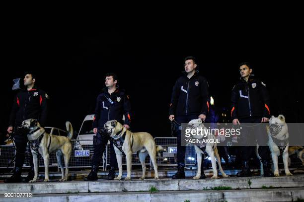 Turkish security force members patrol with their dogs around the city's main Taksim Square as people remember the victims of a deadly New Year's...