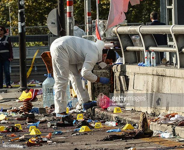 Turkish security forces and forensic police inspect the blast site after an explosion during a peace march on October 10 2015 in Ankara Turkey...
