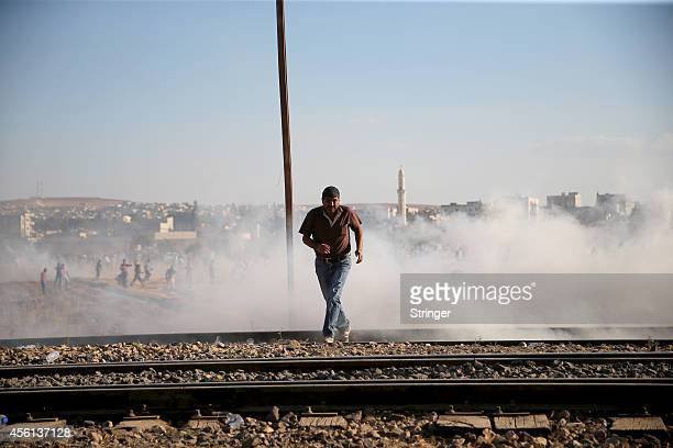 Turkish security forces use teargas to disperse Kurdish demonstrators after they pull down a part of the TurkishSyrian border fence near the...