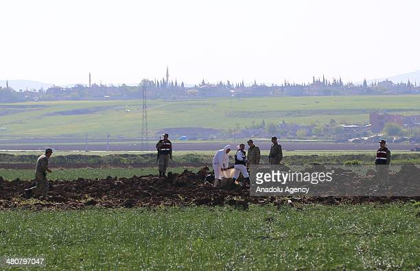 Turkish security guards examine the area after the mortar shells dropped on in an empty land Turkey's Reyhanli region close to the Syrian border in...