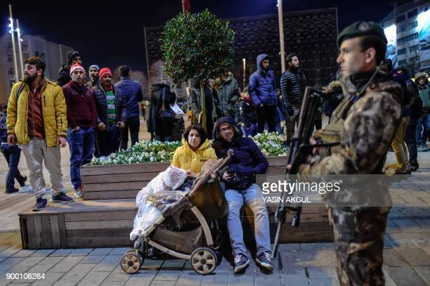Turkish security officers patrol around the city's main Taksim Square as people remember the victims of a deadly New Year's attack a year ago in...