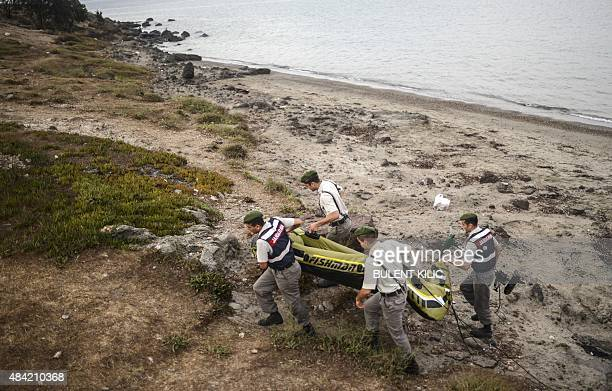 Turkish servicemen carry a boat left by migrants on early August 16 2015 off the shore of Bodrum southwest Turkey Authorities on the island of Kos...