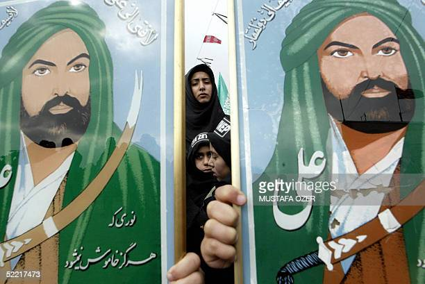 Turkish Shiite girls holds posters of Imam Ali who is son in law of Prophet Mohammed during the mourning of Ashura in Istanbul 19 February 2005 By...