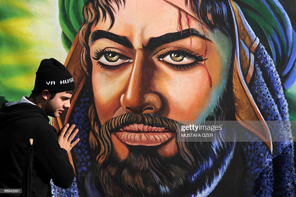 A Turkish Shiite man touches a portrait : News Photo