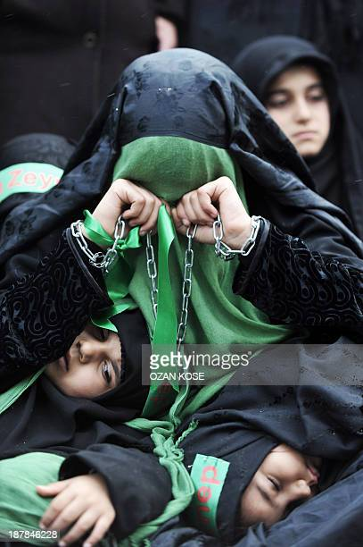 A Turkish Shiite woman holds chains as she takes part in a religious procession held for the Shiite religious holiday of Ashura on November 13 in...