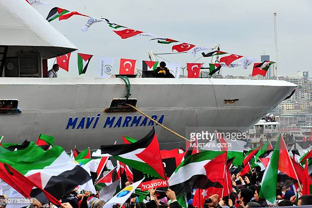 Turkish ship Mavi Marmara arrives at Istanbul's Sarayburnu port as people wave Turkish and Palestinian flags on December 26 2010 The Israeli navy...