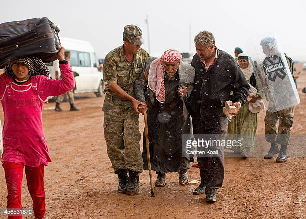 A turkish soldier assist in heavy rain refugees who had arrived from Syria at the border crossing on October 2 2014 near Suruc Turkey The Turkish...