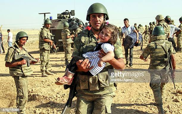 Turkish soldier carries a Syrian girl as she crosses into Turkey with her family from the borderline in Akcakale district of Sanliurfa on June 06...