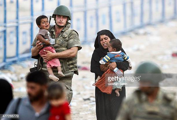 Turkish soldier carries a Syrian refugees boy as they walk to cross into Turkey at Akcakale border gate in Sanliurfa province Turkey June 15 2015...