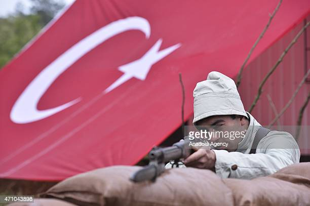 Turkish soldier dressed as World War I Ottoman troops reenacts the Battle of Canakkale as thousands of people walk from the same road that the...