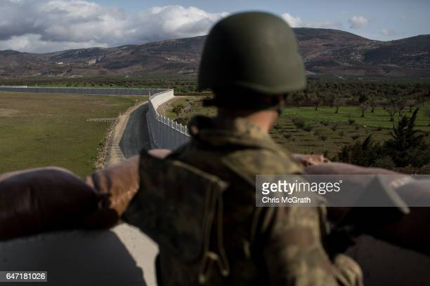 Turkish soldier from the 1st Border Regiment Command looks out over the border wall to Syria during alert drills at a military outpost on the...