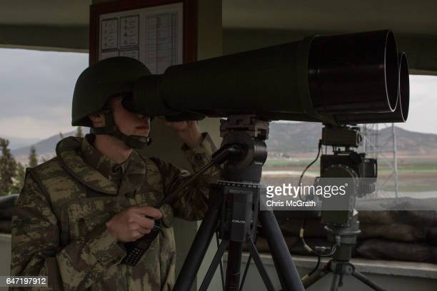 Turkish soldier from the 1st Border Regiment Command uses high powered binnoculars to look out over Syria during alert drills at a military outpost...