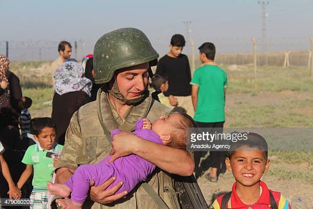 Turkish soldier hold a Syrian baby fled from clashes in Tell Abyad region of Syria carry their belongings after they cross Turkish Syrian border to...