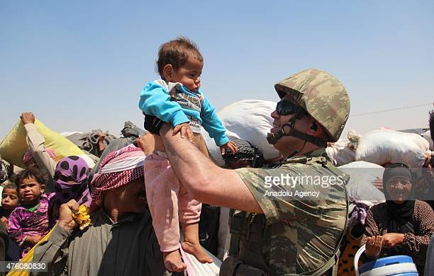 Turkish soldier holds a Syrian baby as Syrians cross into Turkey from the borderline in Akcakale district of Sanliurfa on June 06 2015 Hundreds of...