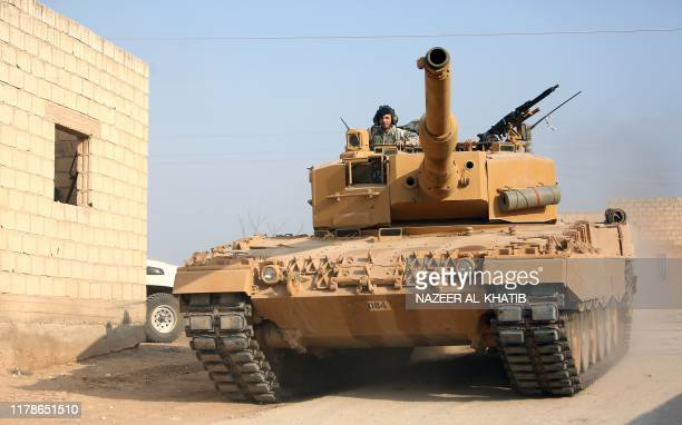 A Turkish soldier mans a tank during a raid in a village east of Ras alAin on the border between Syria and Turkey in northeastern Syria on October 28...