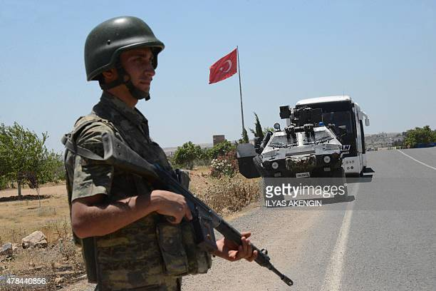 A Turkish soldier stand guard on the way to Mursitpinar crossing gate in Suruc in Turkey's Sanliurfa province across the Syrian border town of Kobane...