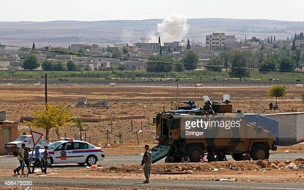 A Turkish soldier stands guarded near an APC in the border as smoke billows from the Syrian beseiged town of Kobane near the southeastern town of...