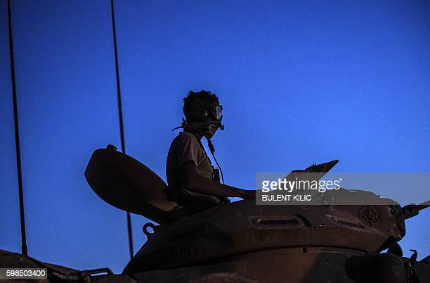 Turkish soldier stands in a Turkish army tank driving back to Turkey from the SyrianTurkish border town of Jarabulus on September 1 2016 in the...