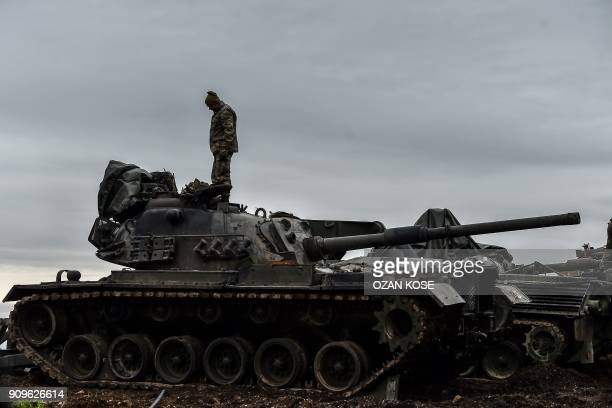 Turkish soldier stands on a tank near the Syrian border at Hassa in Hatay province on January 24 as part of the operation Olive Branch launched a few...