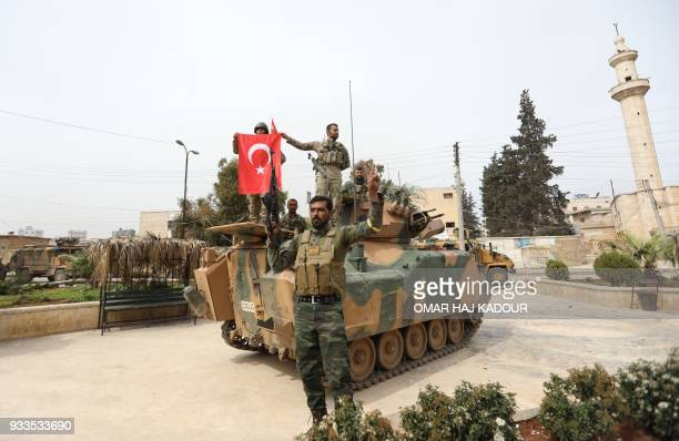 Turkish soldiers and Ankarabacked Syrian Arab fighters pose for a group photo in the Kurdishmajority city of Afrin in northwestern Syria after...