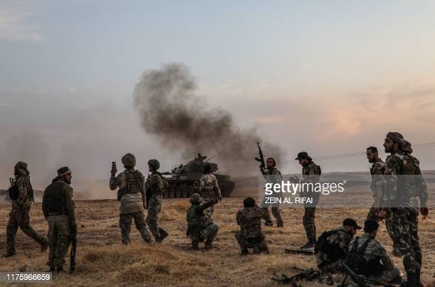 Turkish soldiers and Turkey-backed Syrian fighters gather on the northern outskirts of the Syrian city of Manbij near the Turkish border on October...