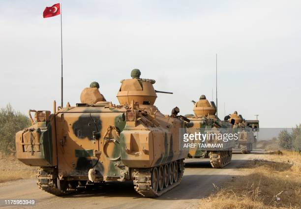 Turkish soldiers are trasported in armoured personnel carriers through the town of Tukhar, north of Syria's northern city of Manbij, on October 14 as...