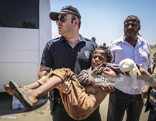 Turkish soldiers carries a wounded Syrian boy who was waiting at the Akcakale Border Gate on his arms in Sanliurfa Turkey on June 16 2015 Hundreds of...