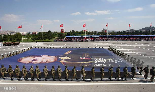 Turkish soldiers carry a giant banner bearing a portrait of Mustafa Kemal Ataturk founder of modern Turkey during a parade marking the 91st...