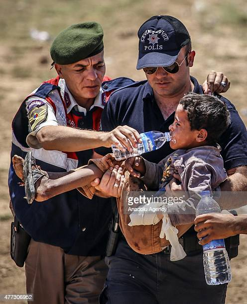 Turkish soldiers gives water to a wounded Syrian boy who was waiting at the Akcakale Border Gate in Sanliurfa Turkey on June 16 2015 Hundreds of...