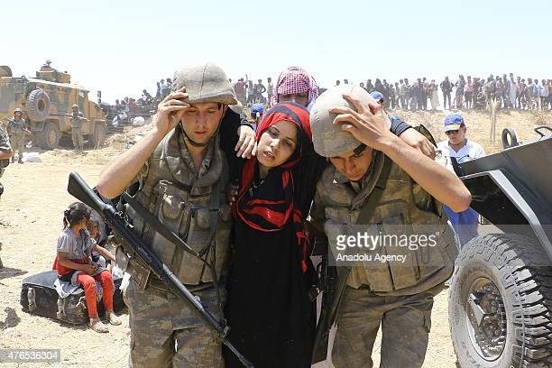 Turkish soldiers help a Syrian woman to cross into Turkey from the borderline in Akcakale district of Sanliurfa on June 10 2015 Hundreds of Syrians...