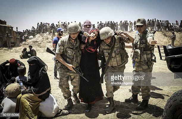 Turkish soldiers help a Syrian woman to cross into Turkey from the borderline in Akcakale district of Sanliurfa on June 10 2015