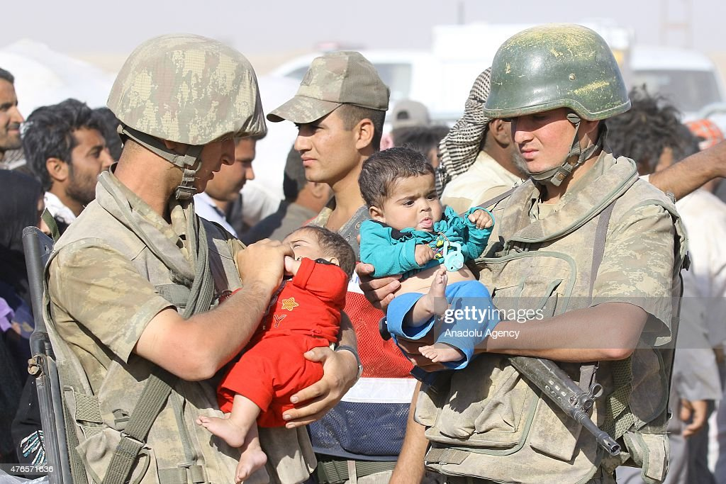 Turkish soldiers help Syrians who fleeing the clashes in Rasulayn region of Syria, cross into Turkey from the borderline in Akcakale district of Sanliurfa on June 10, 2015. Hundreds of Syrians who fled from Syria after clashes in Rasulayn region of Al-Hasakah, have crossed into Turkey since last week.