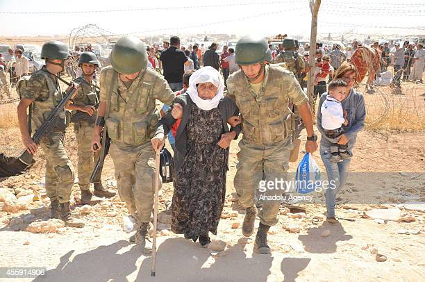Turkish soldiers help the Syrians fleeing clashes between Islamic State of Iraq and the Levant and forces of pro-Kurdish Democratic Union Party as...