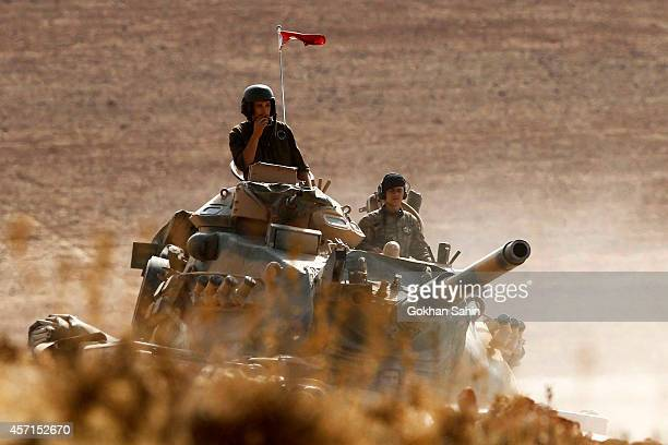 Turkish soldiers hold their position on a tank as they watch the town of Kobani from near the Mursitpinar border crossing, on the Turkish-Syrian...
