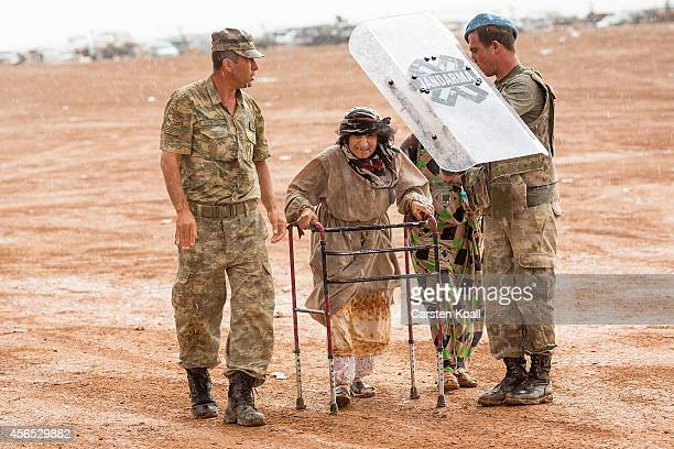 Turkish soldiers holding a shield to protect over the head of an old woman to protect them from the heavy rain after she crossed from Syria into...