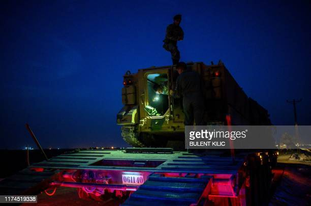 TOPSHOT Turkish soldiers prepare an armoured vehicle as Turkish armed forces drive towards the border with Syria near Akcakale in Sanliurfa province...